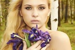 Den härliga blonda kvinnan med blått blommar i en skog Royaltyfri Fotografi