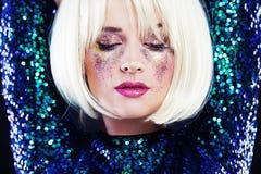 Den härliga blonda kvinnan med partiet blänker makeup Arkivbild