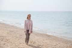 Den härliga blonda kvinnan på stranden är kall fotografering för bildbyråer