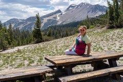 Den härliga blonda kvinnan sitter på en picknicktabell på minaretutsiktsynvinkeln i kolossala sjöar Kalifornien royaltyfria bilder