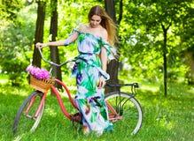 Den härliga blonda kvinnan som bär en trevlig klänning som har gyckel parkerar in, wi Royaltyfria Bilder