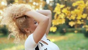 Den härliga blonda kvinnan som trycker på lockigt hår som går i höst, parkerar arkivfilmer