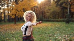 Den härliga blonda kvinnan som trycker på lockigt hår som går i höst, parkerar lager videofilmer