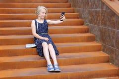 Den härliga blonda preteenflickan som använder en telefon, gör fotoet en främre kamera som sitter på en rostig trappuppgång i en  Royaltyfri Fotografi