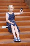 Den härliga blonda preteenflickan som använder en telefon, gör fotoet en främre kamera som sitter på en rostig trappuppgång i en  Royaltyfria Bilder