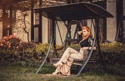 Den härliga blonda rödhåriga kvinnaflickamodellen vilar i alkov för hus för trädgård för gungafartyg Arkivbild