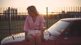 Den härliga blonda unga kvinnan sitter på huven av hennes bil på solnedgången arkivfilmer