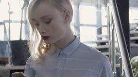 Den härliga blondinen använder smartphonen, medan stå i modernt kontor lager videofilmer