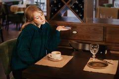 Den härliga blondinen för den unga kvinnan dricker kaffe i ett kafé förvånad sinnesrörelse med telefonen coquette arkivbild