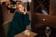 Den härliga blondinen för den unga kvinnan dricker kaffe i restaurang förvånad sinnesrörelse med telefonen coquette fotografering för bildbyråer