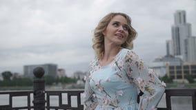 Den härliga blondinen i en blå klänning ler på kameran lager videofilmer