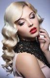 Den härliga blondinen i ett Hollywood sätt med krullning, röda kanter och snör åt klänningen Härlig le flicka arkivfoto