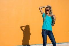 Den härliga blondinen i solglasögon korrigerar lyxigt hår Stående på bakgrunden av den ljusa orange väggen Modern hipster Arkivbilder