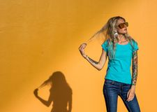 Den härliga blondinen i solglasögon korrigerar lyxigt hår Stående på bakgrunden av den ljusa orange väggen Modern hipster Royaltyfria Bilder