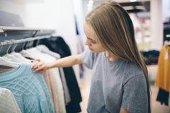 Den härliga blondinen köper ny saker i ett klädlager Säljaren arbetar i boutique Arkivbilder