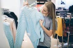 Den härliga blondinen köper ny saker i ett klädlager Säljaren arbetar i boutique Royaltyfri Foto