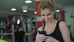 Den härliga blondinen på trampkvarnen använder telefonen och att lyssna till musik 4K stock video
