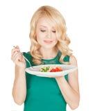 Den härliga blondinen rymmer en platta med sallad från grönsaker Arkivfoton