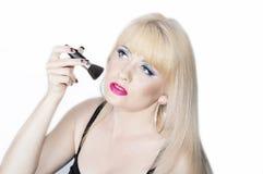 Den härliga blondinen sätter ett smink på en framsida Royaltyfria Bilder