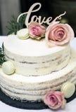 Den härliga bröllopstårtan med kräm med rosa färger för textförälskelse blommar överst rosor Arkivbild