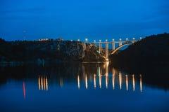Den härliga bron reflekterade i vattnet på natten Royaltyfri Foto