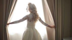 Den härliga bruden öppnar gardinerna i mörkret lager videofilmer