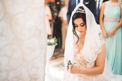 Den härliga bruden får gift i en kyrka royaltyfri fotografi