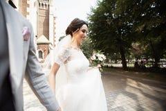 Den härliga bruden går med hans brudgum nära gammal kristen kyrka royaltyfri bild