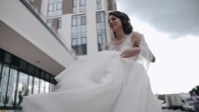 Den härliga bruden går runt om staden som rymmer fållen av hennes klänning h?rligt flickabarn stock video