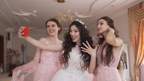 Den härliga bruden har gyckel med två brudtärnor De tar lyckligt selfies på mobiltelefonen Morgon av stock video