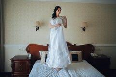 Den härliga bruden i morgonklänningarna för en bröllopceremon royaltyfri foto