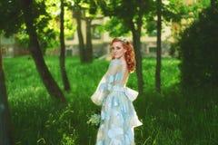 Den härliga bruden i sommar parkerar Rödhårig manflicka i tappningklänning Royaltyfri Foto