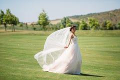 Den härliga bruden i den vita bröllopsklänningen för lyxigt mode med skyler på den gröna golfklubbgläntan, bröllopdag Fantastiskt royaltyfria bilder