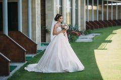 Den härliga bruden i den vita bröllopsklänningen för lyxigt mode med skyler på den gröna golfklubbgläntan, bröllopdag Fantastiskt arkivfoton