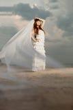 Den härliga bruden med ett långt skyler på stranden på solnedgången Fotografering för Bildbyråer