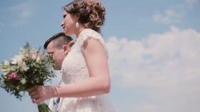 Den härliga bruden och den stiliga brudgummen går i en parkera i sommartid Den vita bröllopsklänningen och kappan, hår-gör steadi arkivfilmer