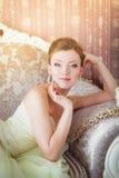 Den härliga bruden sitter på soffan Royaltyfri Foto