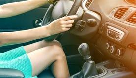 Den härliga brunbrända slanka kvinnachauffören lägger benen på ryggen i en bil Flicka i klänningen som kör en bil royaltyfri fotografi
