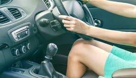 Den härliga brunbrända slanka kvinnachauffören lägger benen på ryggen i en bil Flicka i klänningen som kör en bil arkivbilder