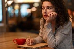 Den härliga brunettaffärskvinnan gör anmärkningar i hennes notepad i hemtrevlig restaurang iklädda grå färger stucken sweather royaltyfri fotografi