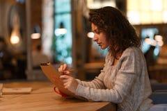 Den härliga brunettaffärskvinnan gör anmärkningar i hennes notepad i hemtrevlig restaurang iklädda grå färger stucken sweather arkivbilder
