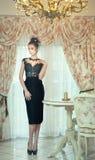 Den härliga brunettdamen i elegant svart snör åt klänningen som poserar i en tappningplats Ung sinnlig trendig kvinna på höga häl Arkivbilder