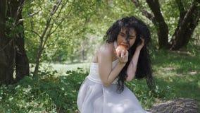 Den härliga brunetten äter det röda äpplet i trädgården arkivfilmer