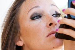 Den härliga brunetten applicerar ögonskugga. Arkivfoto