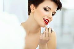 Den härliga brunetten applicerar läppstift.  Röda kanter Royaltyfria Bilder