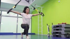 Den härliga brunetten gör squatting med bälten i idrottshallen lager videofilmer