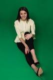 Den härliga brunetten i en gul blus och svart flåsar på en gräsplan fotografering för bildbyråer
