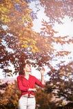 Den härliga brunetten kopplar av i sidor nära ett träd Royaltyfri Foto