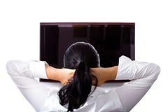 Den härliga brunetten kopplar av på TV:N Royaltyfri Fotografi