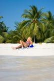 Den härliga brunetten ligger på en vit strand Arkivfoto